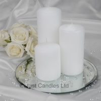 A white coloured wedding centrepiece pillar candle set with optional glass mirror plate